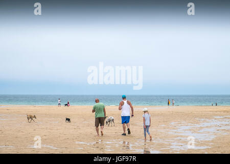 People on a beach.  Holidaymakers walking along the beach at Harlyn Bay on the North Cornwall coast. - Stock Photo