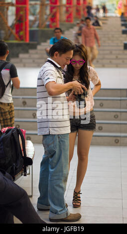 Photographer and model checking images on back of camera during open-air shoot. Bangkok, Thailand - Stock Photo