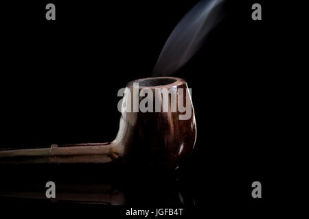 Lit Tobacco Smoking pipe reflective glass surface, with moving smoke, low key black background - Stock Photo