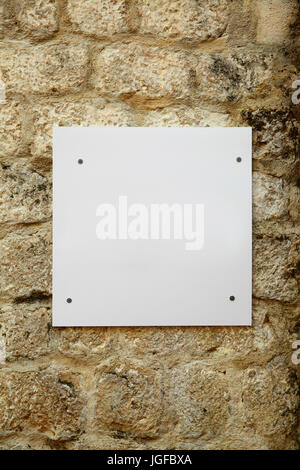 White blank signboard on old stone wall - Stock Photo