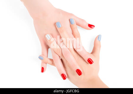 Woman connected hands with red and blue shellac nail polish. Isolated on white, clipping path included - Stock Photo