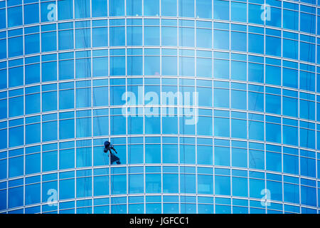 Industrial climber wash the windows of modern skyscraper. Blue toned image - Stock Photo