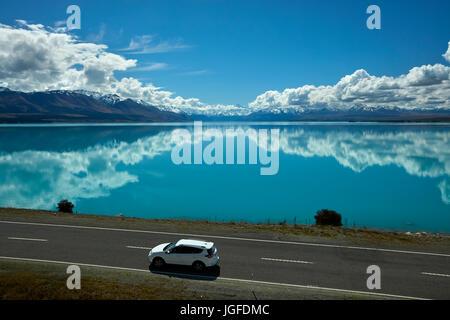 SUV on State Highway 8, and Aoraki / Mount Cook reflected in Lake Pukaki, Mackenzie Country, Canterbury, South Island, - Stock Photo