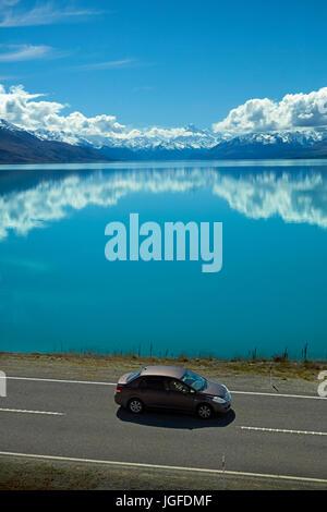 Car on State Highway 8, and Aoraki / Mount Cook reflected in Lake Pukaki, Mackenzie Country, Canterbury, South Island, - Stock Photo