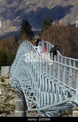 Tourists on pedestrian Bridge over Lake Tekapo outlet to Church of the Good Shepherd,  Mackenzie Country, Canterbury, - Stock Photo