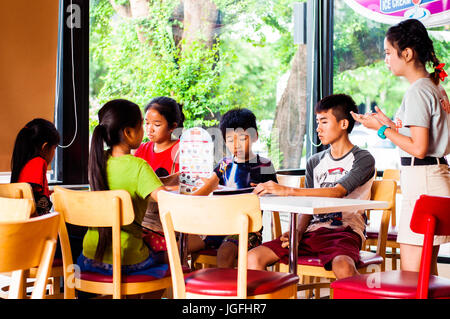 Children in Swensons icecream parlor, Vientiane, Laos - Stock Photo