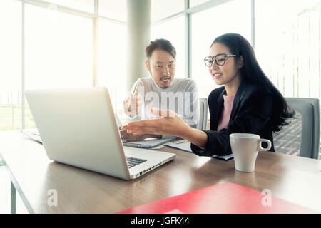 Couple of young designers working at modern office, two coworkers discussing fun project over a laptop, little team - Stock Photo