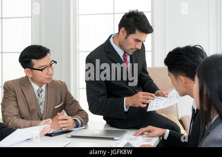 Asian smart manager explaining internal meeting to his project team in modern office. The multi ethnic business - Stock Photo