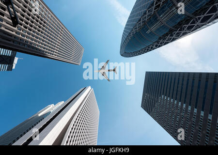 Tokyo skyscrapers buildings and a plane flying overhead at in Tokyo Shinjuku downtown and business district in morning - Stock Photo