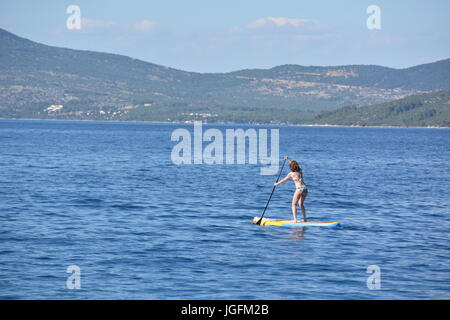 Cres, Croatia - June 18, 2017 - Girl on stand up paddleboard - Stock Photo