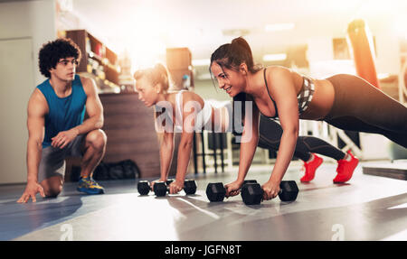 Two smiling girl exercising at the gym with a personal trainer. - Stock Photo