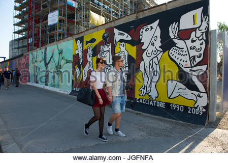 A couple walks past the East Side Gallery in Berlin, a 1.3 km long, painted section of the Berlin Wall and an international - Stock Photo