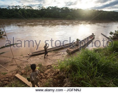 Tsimane people approach a canoe to transport goods on the Maniqui River, near Anachere, in the Amazon rainforest, - Stock Photo
