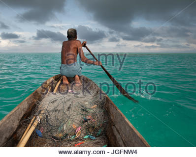 A Bajau man sets out in his dugout to fish off Bodgaya Island. - Stock Photo