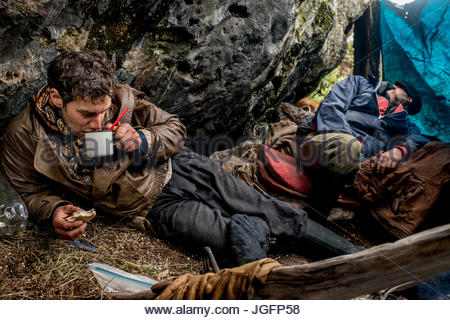 Bagualeros, cowboys who capture feral livestock, drink mate tea while camping on a ranch to ranch trip. - Stock Photo