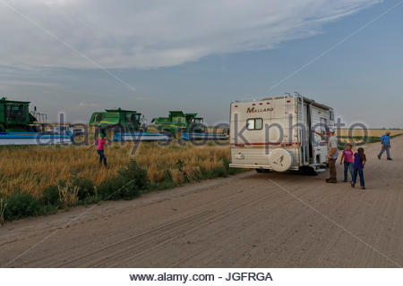A family parks an RV in the field during the harvest so they can escape the elements and the bugs while they eat. - Stock Photo