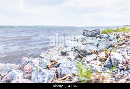 Colorful rocks on Saint Laurent or Lawrence river in Quebec, Canada during summer with grass and water - Stock Photo