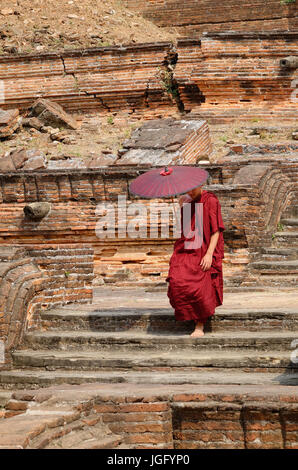 A monk in the red robe with umbrella walking down stairs at the pagoda. - Stock Photo