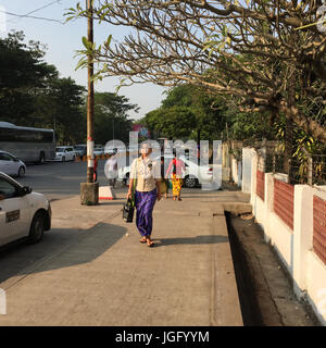 Yangon, Myanmar - Feb 13, 2017. People walking on main street at business district in Yangon, Myanmar. Yangon is - Stock Photo