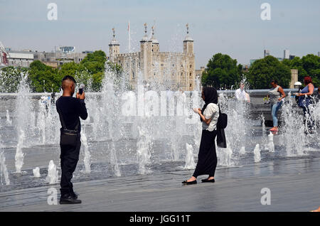 London, UK. 6th July, 2017. Selfie in front of the fountain at City Hall. tPeople enjoying the sunshine while watching - Stock Photo