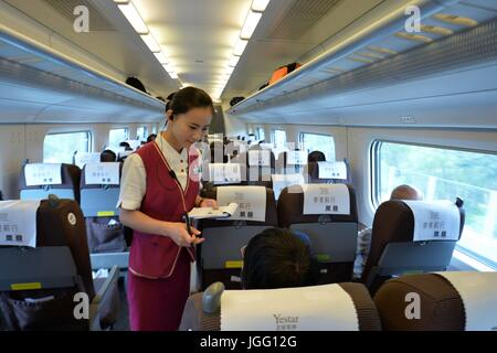 Xiongan, China's Hebei Province. 6th July, 2017. A conductor checks passengers' tickets on the bullet train D6655, - Stock Photo