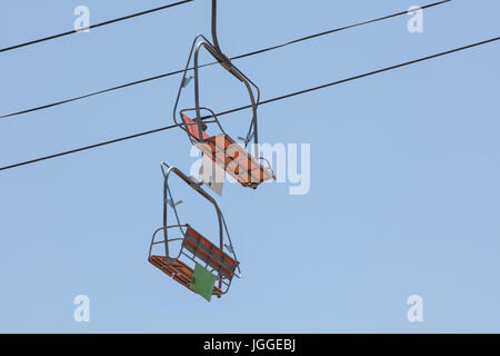 Orange chairlift at an amusement park running on steal cables - Stock Photo
