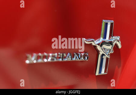 Logo on the door of a vintage red Ford Mustang - Stock Photo
