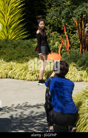 woman photographing daughter in Chihuly Garden and Glass, Seattle Center, Washginton State - Stock Photo