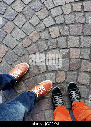 Legs and feet of two people wearing sneakers standing on cobblestone pavement from above with copy space - Stock Photo