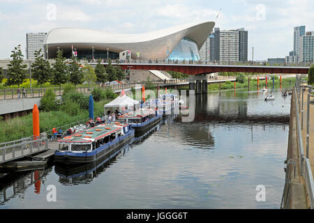 River Lea flowing through the Queen Elizabeth Olympic Park landscape and the Aquatics Centre Stratford, Newham East - Stock Photo