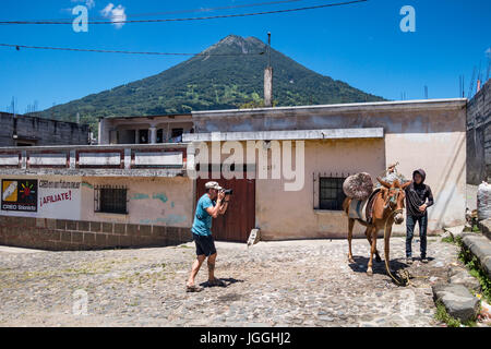 A photographer taking picture of a local man from Guatemala, while charging his donkey (mule) in Guatemala - Stock Photo