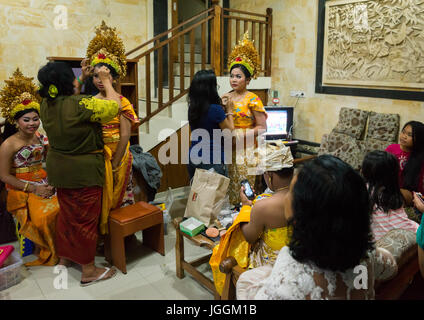 Women applying makeup to teenager girls in traditional costumes before a tooth filing ceremony, Bali island, Canggu, - Stock Photo