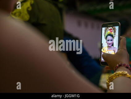 A teenage girl in traditional costume making a selfie before a tooth filing ceremony, Bali island, Canggu, Indonesia - Stock Photo