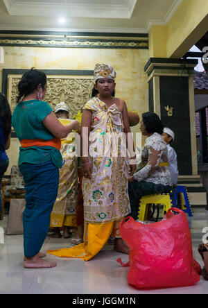 A teenage boy dressed in traditional costume before a tooth filing ceremony, Bali island, Canggu, Indonesia - Stock Photo