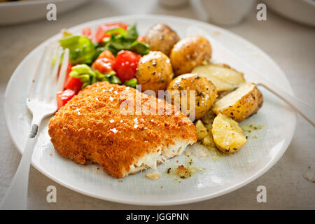 Traditional breaded fillet of cod with baby potatoes and salad - Stock Photo