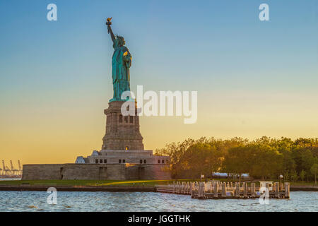 Magnificence of Statue of Liberty at sunset. New York City, USA - Stock Photo