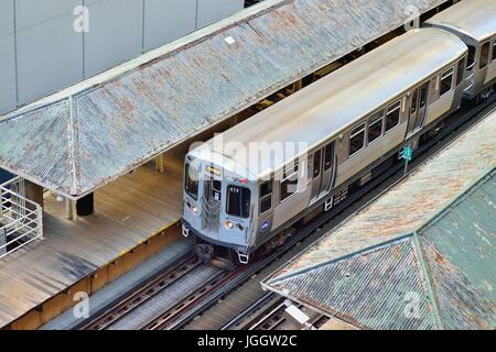 On tracks that form the Loop that defines Chicago's famous downtown area, a CTA rapid transit train paused at a - Stock Photo