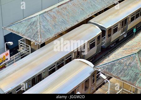 On tracks that gave rise to the term Loop in Chicago's famous downtown area, a pair of CTA rapid transit trains - Stock Photo