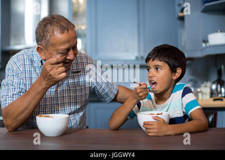Grandfather and grandson having breakfast at home - Stock Photo