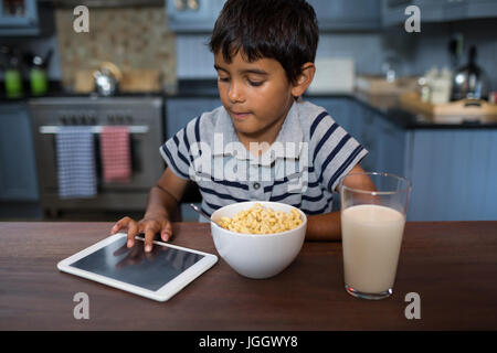 Boy using tablet computer while having cereal breakfast at home - Stock Photo