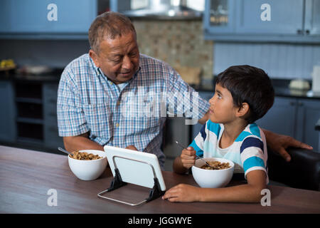Grandfather and grandson using tablet computer while having breakfast at home - Stock Photo