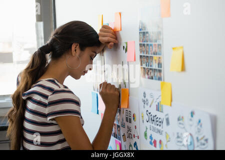 Tired young woman leaning on wall with sticky notes in creative office - Stock Photo