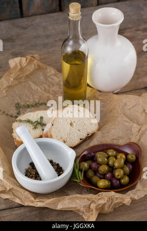 High angle view of olives with oil bottle and bread by spices in mortar pestle on table - Stock Photo