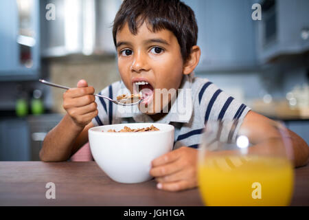 Close up portrait of boy looking away while having breakfast at home - Stock Photo