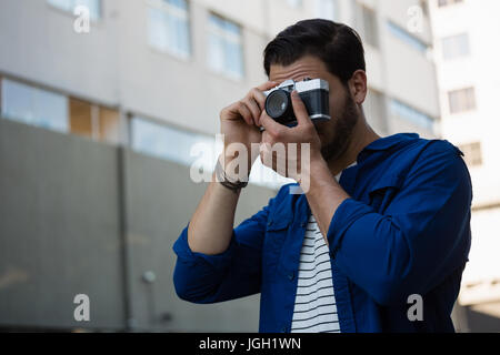Young man photographing through camera while standing by building - Stock Photo
