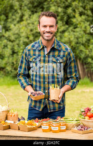 Portrait of smiling young man selling organic vegetables at farm - Stock Photo