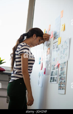 Exhausted woman standing by sticky notes in creative office - Stock Photo