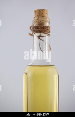 Close up of olive oil bottle with cork on table - Stock Photo
