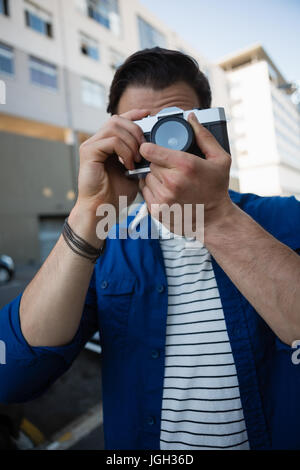 Close up of man photographing through camera while standing by building - Stock Photo