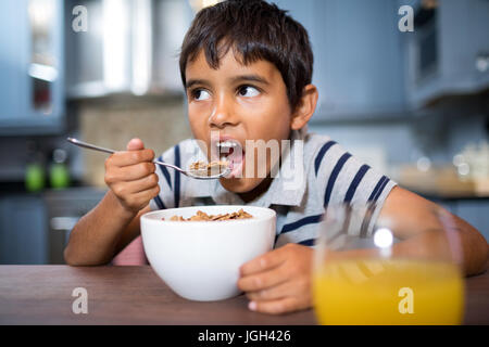 Close up of boy looking away while having breakfast at home - Stock Photo